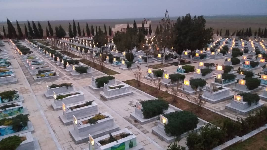 Photo of PYD youth in Resistance Campaign lit candles on tombs of martyrs
