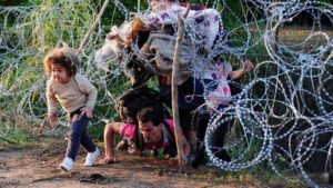 A migrant's family creeps under a barbed fence near the village of Roszke, at the Hungarian-Serbian border on August 27, 2015. As Hungary scrambles to ramp up defences on its border with Serbia, refugees continued to surge into the country in record numbers, police figures confirmed. AFP PHOTO / CSABA SEGESVARI        (Photo credit should read CSABA SEGESVARI/AFP/Getty Images)